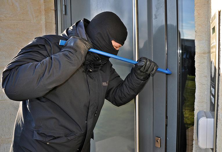 Un ladrón forzando la puerta de una casa.